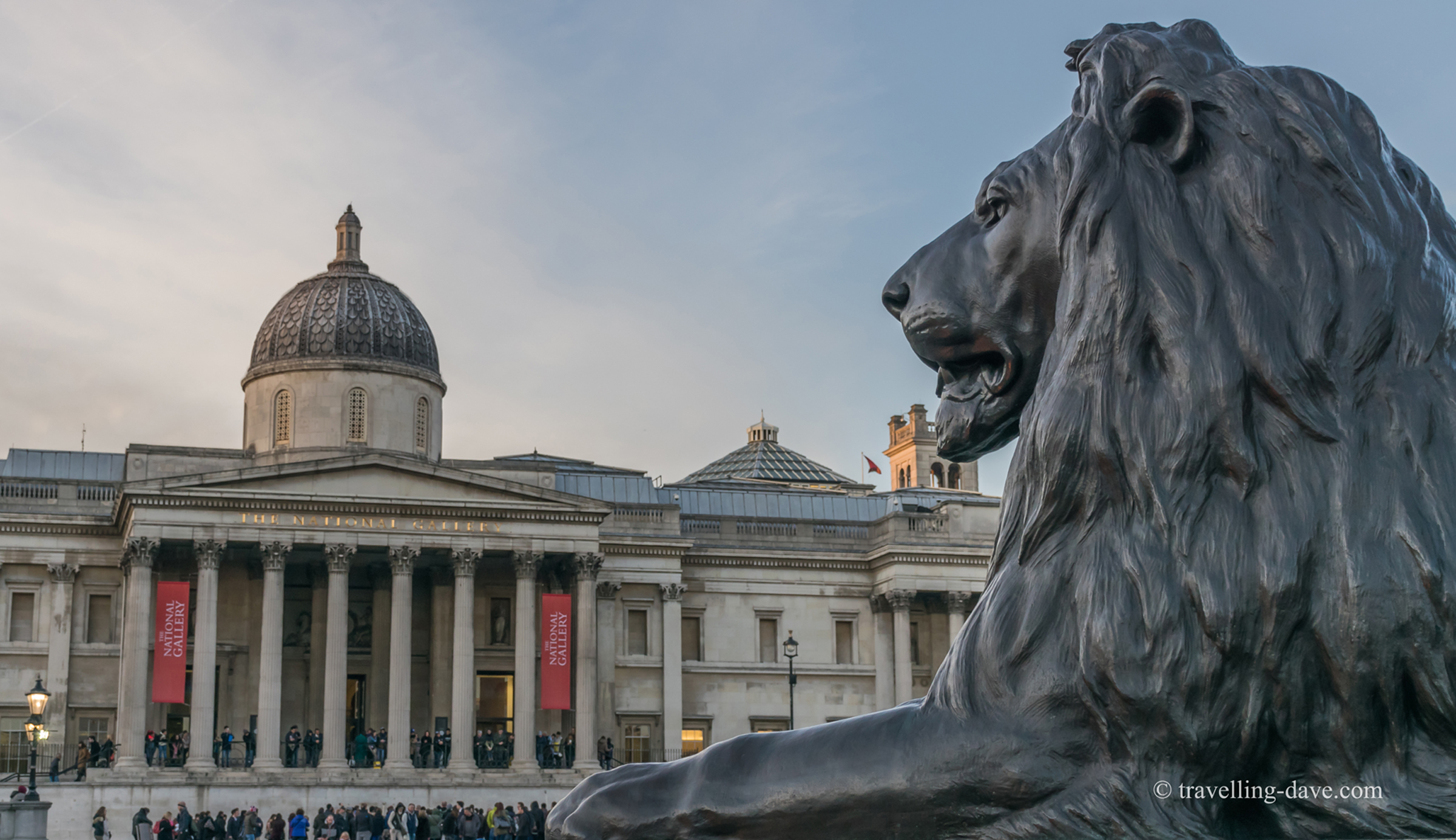 View of one of the lion statues and the National Gallery in London's Trafalgar Square