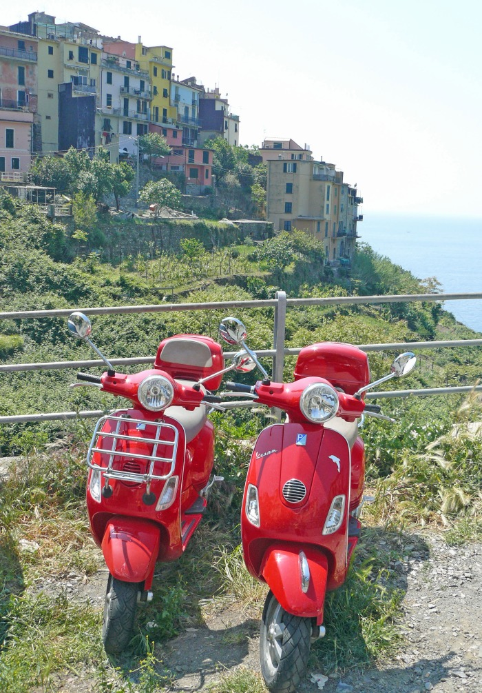 Two red mopeds with the village of Corniglia in the background
