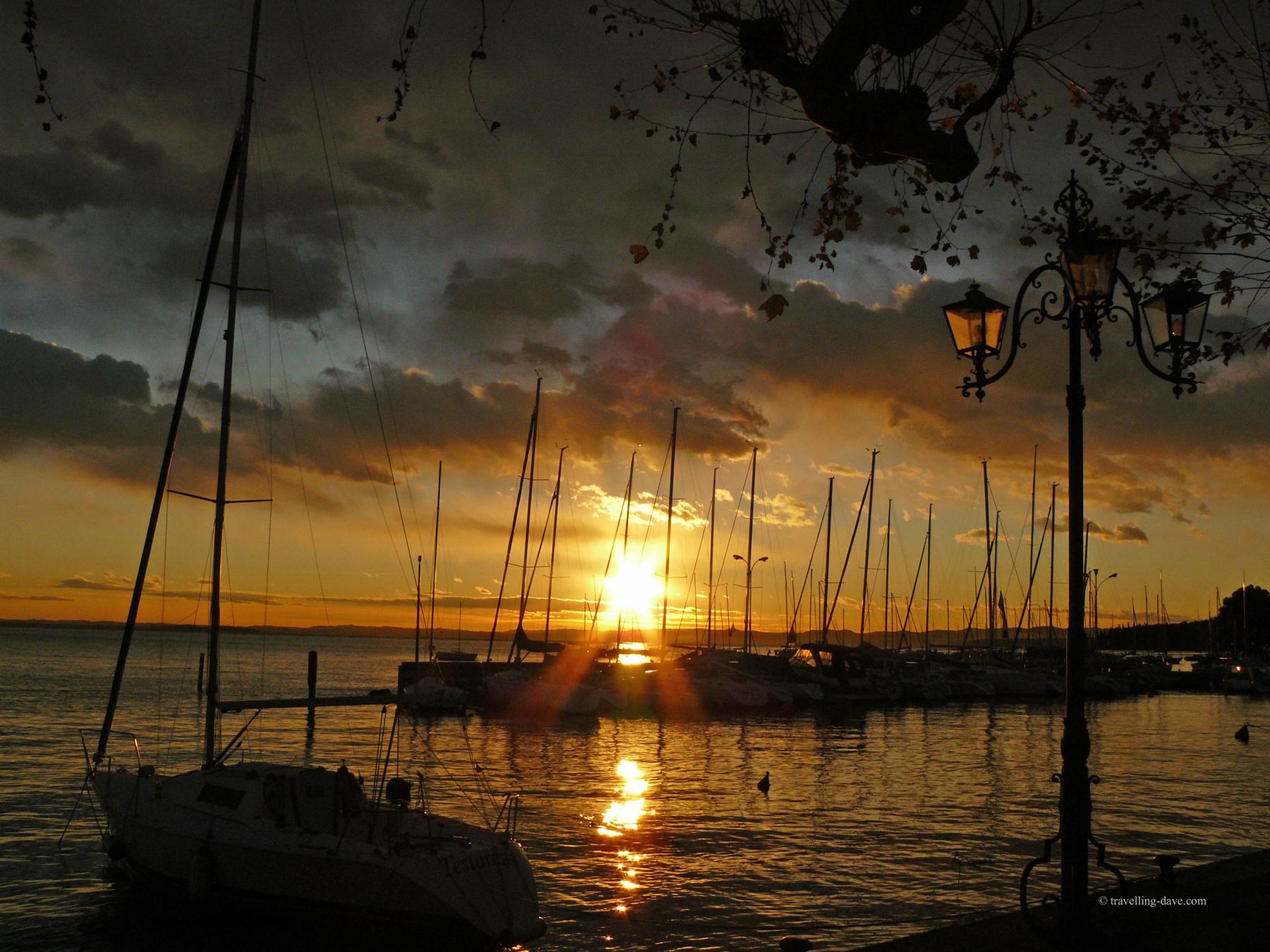 Sun setting on Garda's harbour in Italy