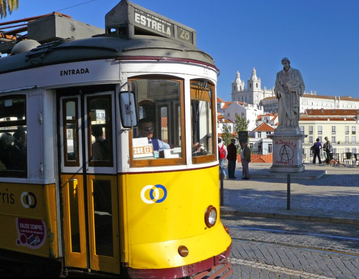 Statue and yellow tram in Lisbon