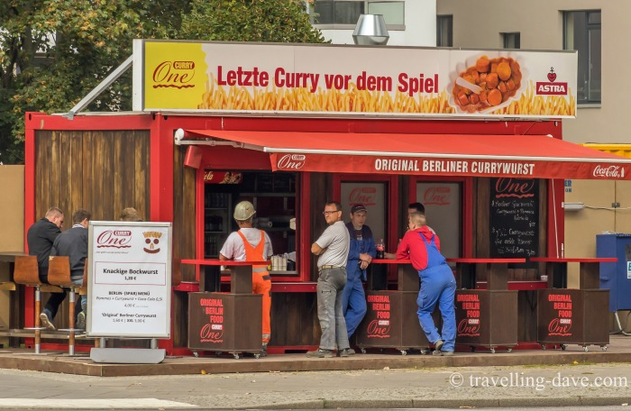 People outside a currywurst kiosk