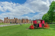 View of a red carriage and Hampton Court Palace