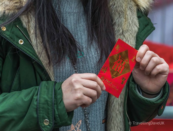 A woman holding a red envelope for Chinese New Year