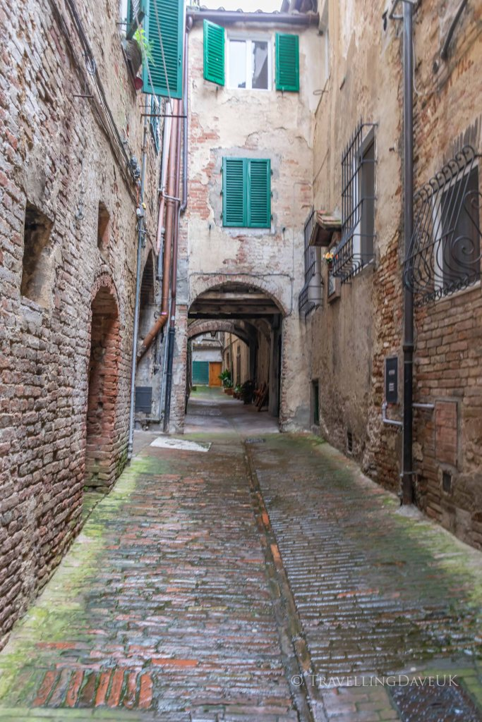 View of a narrow cobbled street in Siena in Italy