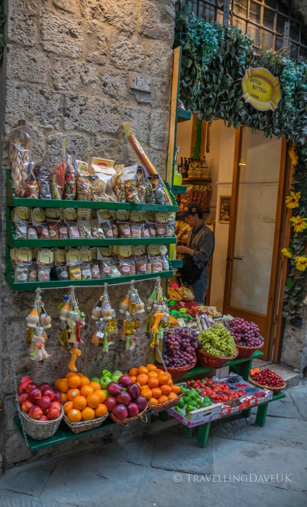 View of a colourful display outside a fruit and veg shop in Siena in Italy