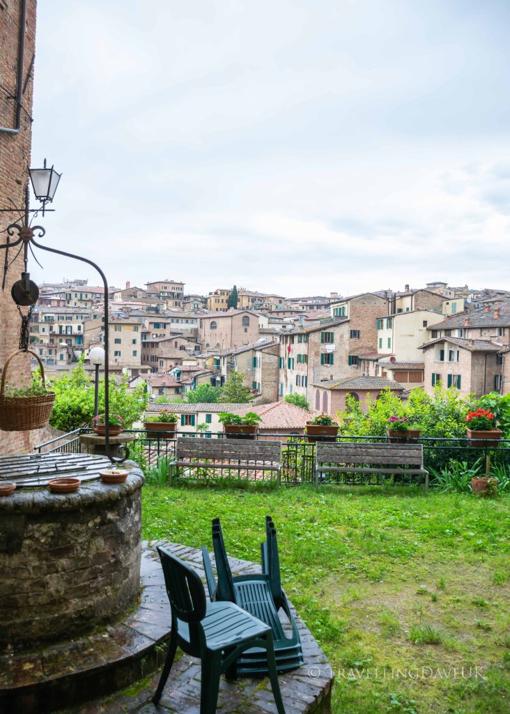 View of Siena rooftops in Italy from a garden with a well